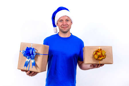 A happy courier in a blue uniform and Santa hat holds two gift boxes with bows. New year and merry Christmas. The man smiles. Secure contactless remote delivery of holiday gifts during coronavirus.