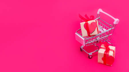 Small grocery cart with gift boxes on red-pink background. Give gifts with love on Valentines Day, Christmas and birthday. Shopping online. Holiday sales and discounts. Retail and wholesale purchase.