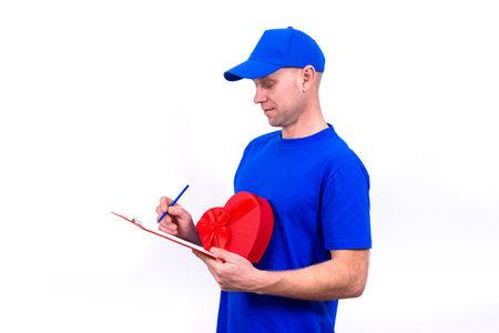 在蓝色制服的快递拿着红色心形的礼物盒为情人节和检查订单在剪贴板。在母亲和国际妇女节上的家庭送货礼物给您最喜欢的女性和国际妇女节。