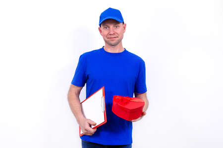 Courier in blue uniform holds a red heart-shaped gift box for Valentines Day. Home delivery of holiday gifts to your favorite women on Mothers and International Womens Day. Man smiles. I love you.