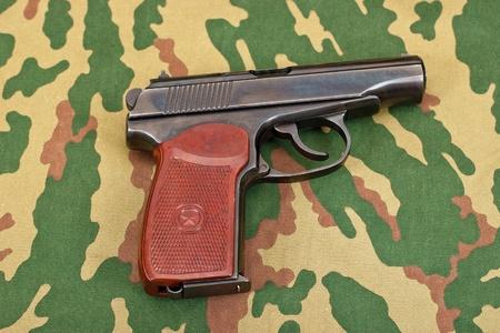 camouflaged: Army handgun on camouflaged background