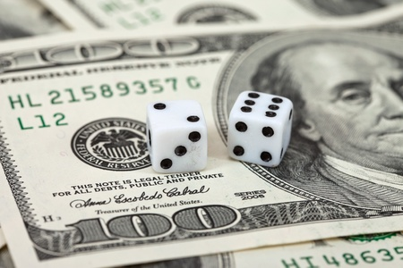 Two dice laying over a pile of money photo