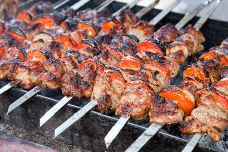 Juicy slices of meat with sauce prepare on fire (shish kebab) photo