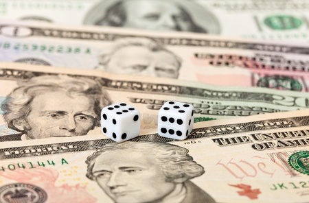 Two dice laying over a pile of money Stock Photo - 10749256