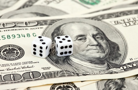Two dice laying over a pile of money Stock Photo - 11307055