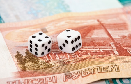 Two dice laying over a pile of money Stock Photo - 11307054