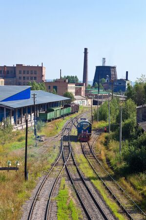 Industrial landscape with chimneys and train.