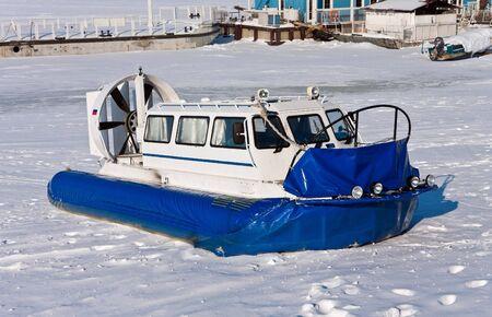 aéroglisseur: Hovercraft traversée de la rivière gelée contre un ciel bleu