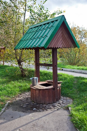 Countryside water well with a bucket. Stock Photo