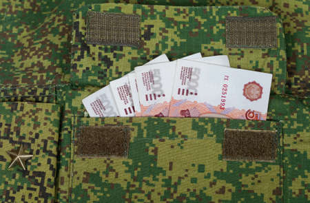 Banknotes in the military uniform pocket  photo