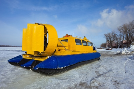 Hovercraft crossing frozen river against blue sky Stock Photo - 12514790