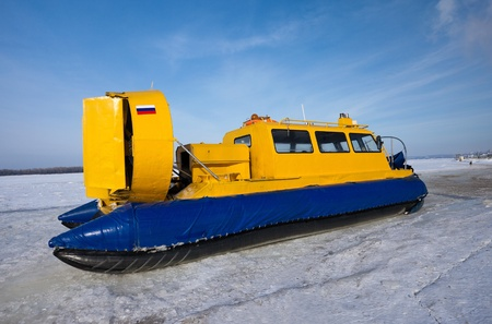Hovercraft crossing frozen river against blue sky photo