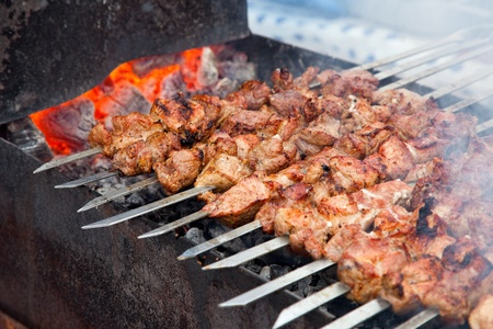 Appetizing fresh meat shish kebab  shashlik   prepared on a grill wood coal, outdor photo