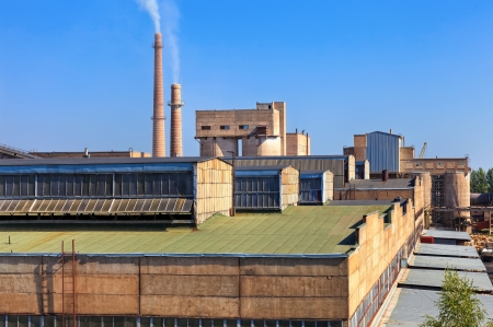 Large factory with smoking chimneys against the blue sky