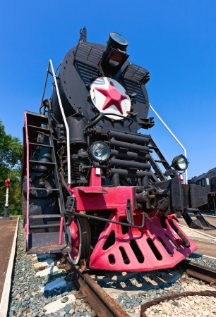 Old steam locomotive with red star against blue sky background