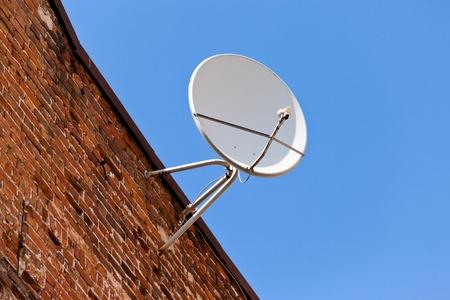 Satellite Dish mounted on old brick wall  photo