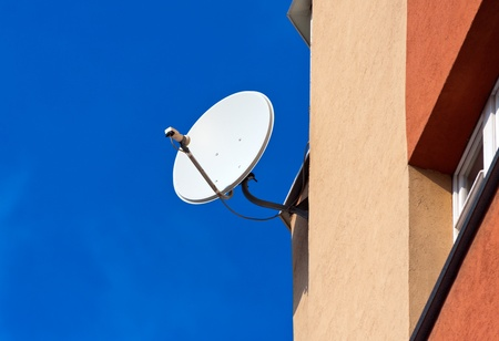 Satellite Dish mounted on  brick wall against blue sky background photo