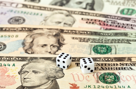 Two dice laying over a pile U.S. dollars Stock Photo - 17433866