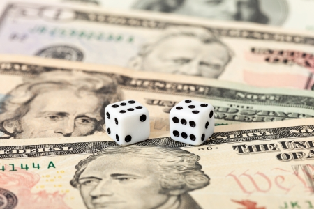 Two dice laying over a pile U.S. dollars Stock Photo - 17433863
