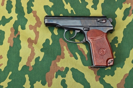 Army handgun on camouflaged background Stock Photo - 17724780