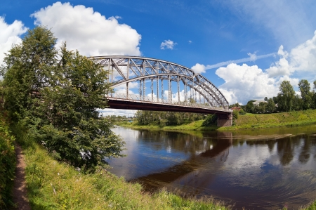 Steel Arch Bridge on river Msta. Novgorod region, Russia. Stock Photo