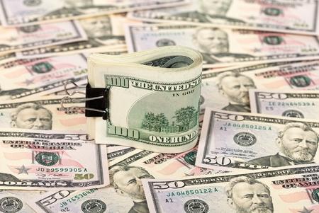 Folded hundred dollar bill on money background Stock Photo