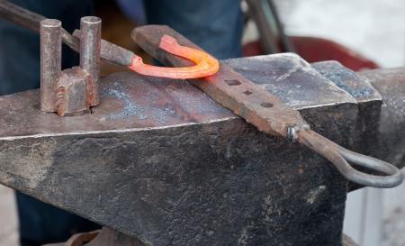 Blacksmith forging a horseshoe on an anvil
