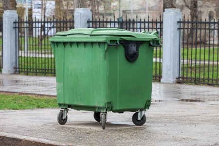 Green recycling container on the street of city