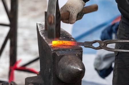 Blacksmith forges iron in the forge Standard-Bild