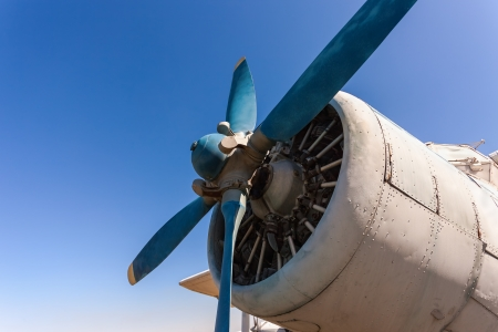 Propeller and engine of old airplane against blue sky