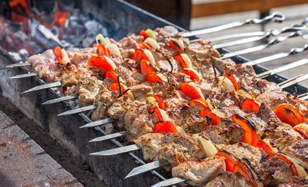 Shish kebab: slices of meat with sauce preparing on fire photo