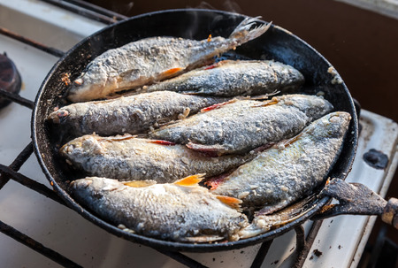 Fried fish in the old frying pan Stock Photo - 22257236