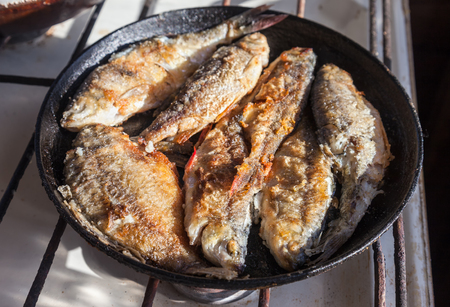 Fried fish in the old frying pan Stock Photo - 22257274