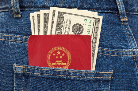 Chinese passport and dollar bills in the back jeans pocket photo
