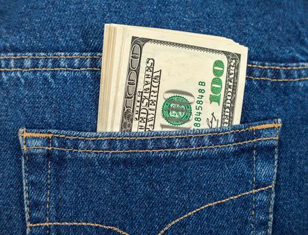 Stack of hundred dollar bills in the back jeans pocket photo