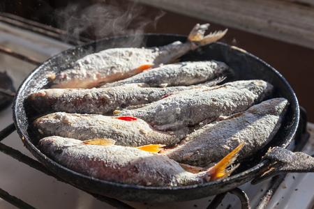 Fried fish in the old frying pan Stock Photo - 22427672