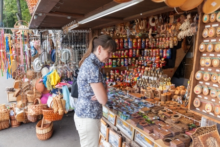matroshka: NOVGOROD - AUGUST 10: Young woman choose Russian handmade souvenirs at the gift shop on August 10, 2013 in Novgorod. Novgorod - famous ancient Russian city