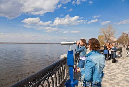 SAMARA, RUSSIA - MAY 1: Girl looks through the coin operated binocular on the banks of the Volga River on May 1, 2013 in Samara, Russia. Volga river is one of the largest rivers in Europe