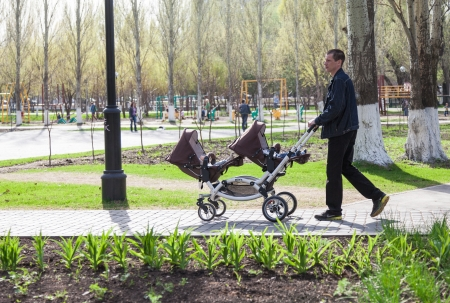 SAMARA, RUSSIA - MAY 3: Father with a baby stroller for twins walk in the park on May 3, 2013 in Samara, Russia.