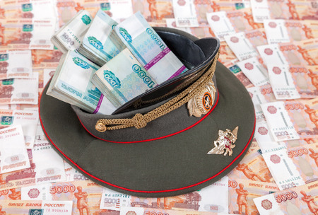 object oppression: Stack of bundled russian ruble banknotes in the officers cap