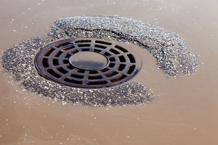 Melted water flows down through the manhole cover on spring day Stock Photo