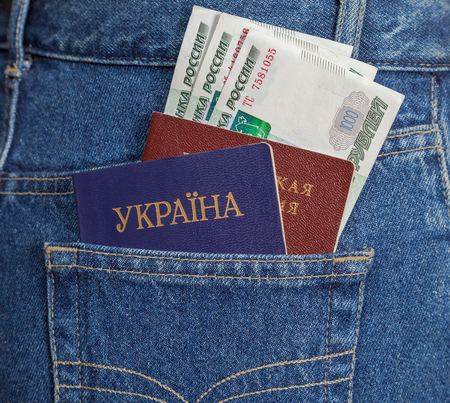 Ukrainian and Russian  passports in the back jeans pocket photo