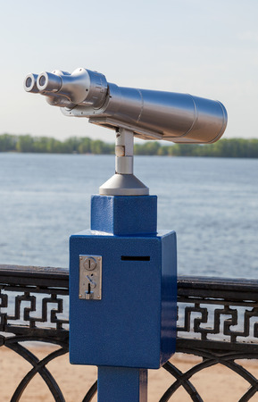 Coin operated binocular on the bank of river photo