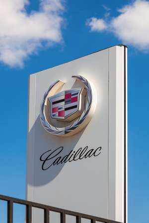 headquartered: SAMARA, RUSSIA - MAY 24, 2014: The emblem Cadillac over blue sky. Cadillac Motor Car Division is a American premium car manufacturer headquartered in Detroit, Michigan, United States