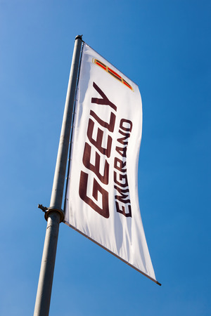 headquartered: SAMARA, RUSSIA - MAY 25, 2014: The flag of Geely over blue sky. Geely is a Chinese automotive manufacturing company headquartered in Binjiang District, Hangzhou, China Editorial