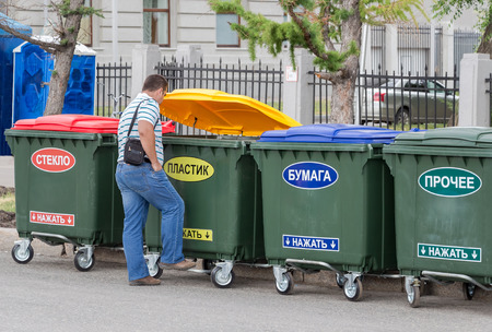 SAMARA, RUSSIA - JUNE 12, 2014: Man throws trash in the dumpster with inscription on russian:  Plastic