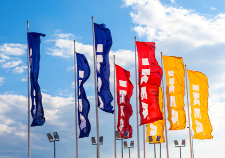 SAMARA, RUSSIA - SEPTEMBER 6, 2014: IKEA flags against sky at the IKEA Samara Store. IKEA is the worlds largest furniture retailer. It was founded in Sweden in 1943