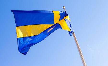 Flag of Sweden waving against blue sky photo