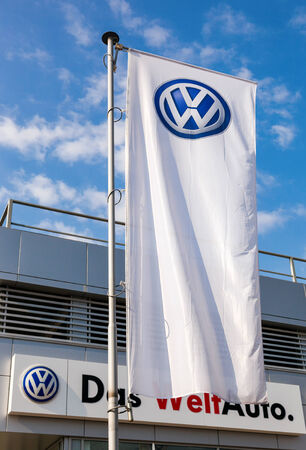 automaker: SAMARA, RUSSIA - SEPTEMBER 21, 2014: The flag of Volkswagen over blue sky. Volkswagen is the biggest German automaker and the third largest automaker in the world