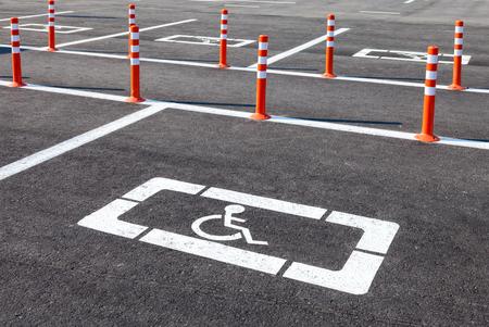 White wheelchair icon on a gray asphalt parking lot photo